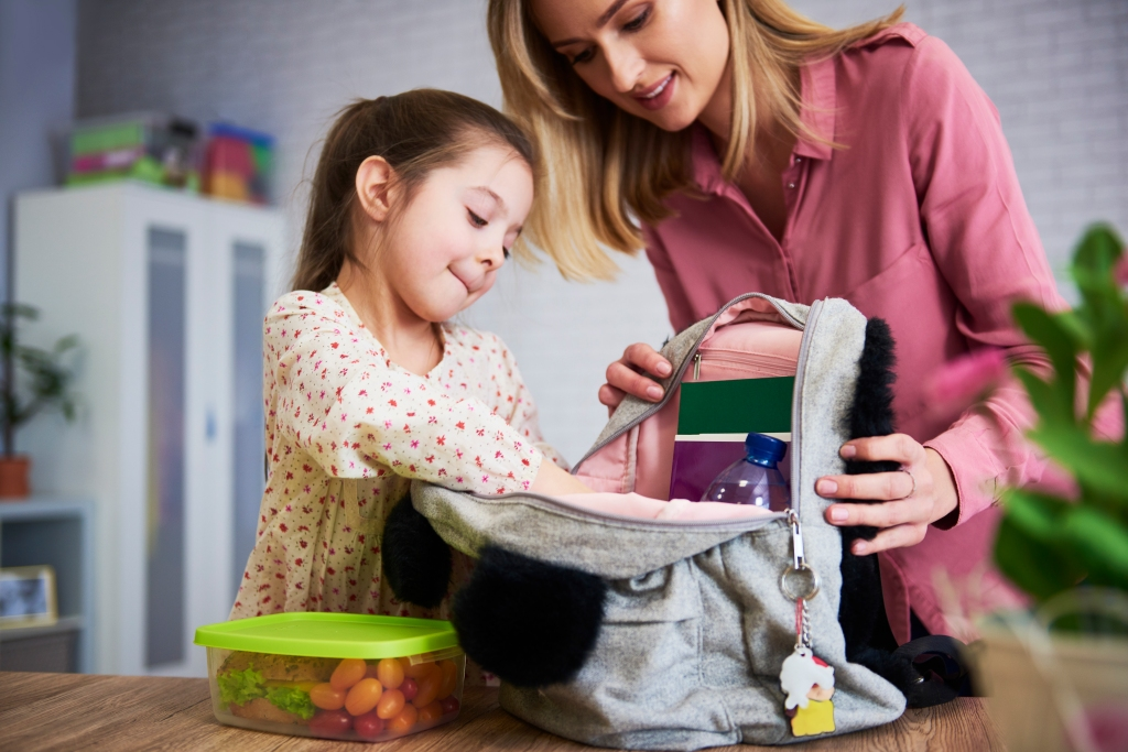 Young mom and daughter packing backpack for the school